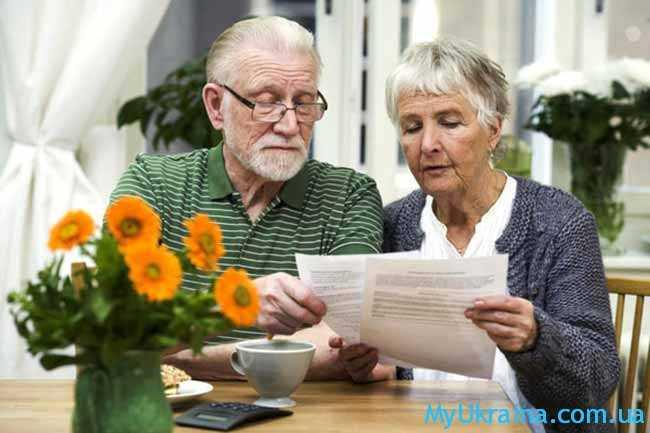 пенсионеры просматривают бумаги
